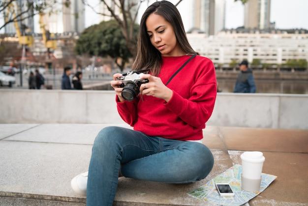 Portret van jonge fotograafvrouw die een professionele digitale camera in openlucht gebruikt. fotografie concept