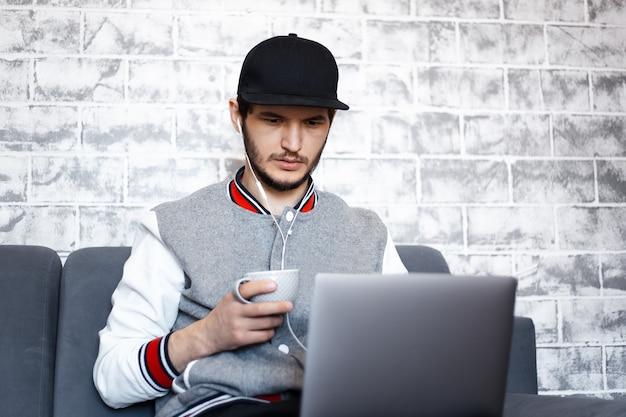 Portret van jonge freelancer man, zittend op de bank met kopje koffie in de hand en laptop op benen. grijze bakstenen muur.