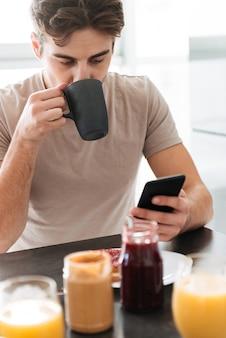 Portret van jonge geconcentreerde man het drinken van thee en het gebruik van smartphone
