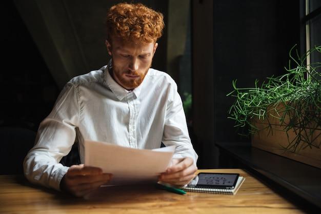 Portret van jonge geconcentreerde readhead gebaarde mens, die bij houten lijst zitten terwijl thuis het werken