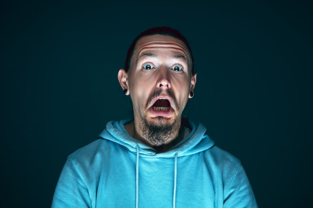 Portret van jonge gekke bang en geschokt blanke man geïsoleerd op donkere achtergrond close-up.