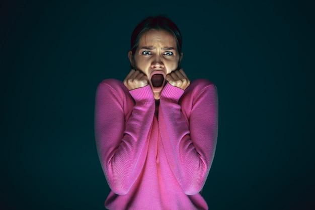 Portret van jonge gekke bang en geschokt blanke vrouw geïsoleerd op donkere achtergrond close-up.