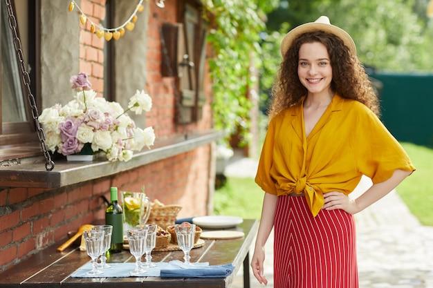 Portret van jonge gekrulde harige vrouw die lacht terwijl poseren door tafel op buiten feestje in de zomer