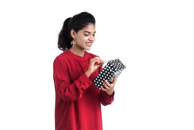 Portret van jonge gelukkig lachend meisje bedrijf en poseren met geschenkdozen op een witte achtergrond.