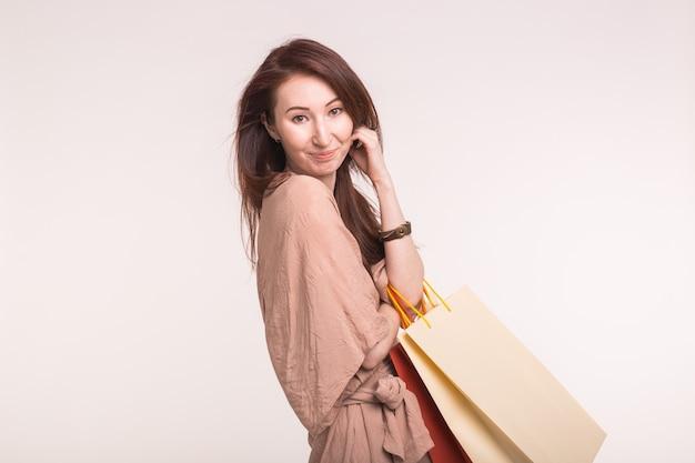Portret van jonge gelukkig lachende aziatische vrouw met boodschappentassen op witte achtergrond