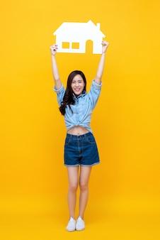 Portret van jonge gelukkig lachende aziatische vrouw met papier thuis
