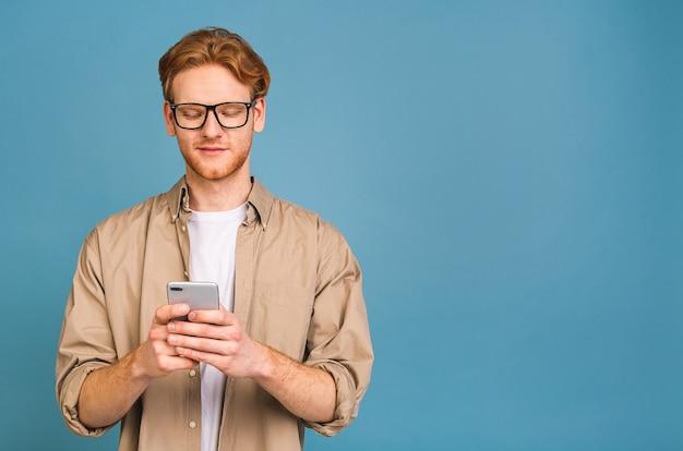 Portret van jonge gelukkig lachende man in casual sms te typen. telefoon gebruiken.