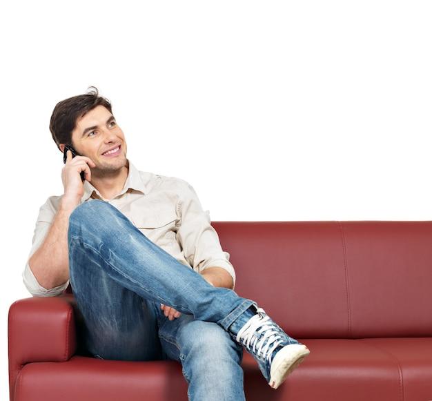 Portret van jonge gelukkig lachende man zit op divan en spreekt op mobiele telefoon, geïsoleerd op wit.
