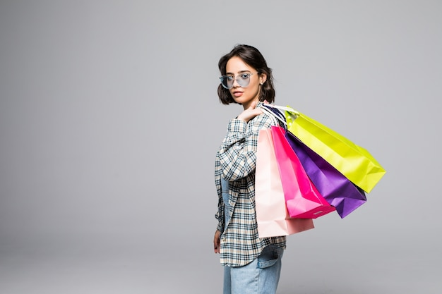Portret van jonge gelukkig lachende vrouw in zonnebril met boodschappentassen geïsoleerd op grijs. verkoop concept.