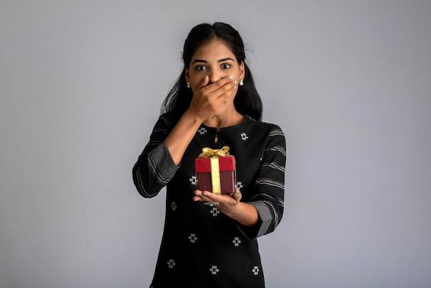 Portret van jonge gelukkig lachende vrouw meisje met geschenkdoos op een grijze achtergrond.
