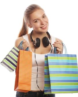 Portret van jonge gelukkig lachende vrouw met boodschappentassen, geïsoleerd op witte achtergrond