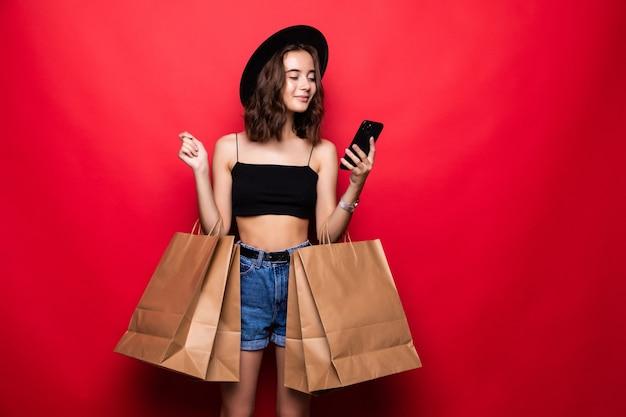 Portret van jonge gelukkig lachende vrouw met boodschappentassen, met copyspace lege lege ruimte voor tekst of slogan, bellen via mobiele telefoon, tegen rode muur
