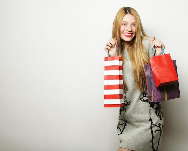 Portret van jonge gelukkig lachende vrouw met boodschappentassen, op witte achtergrond