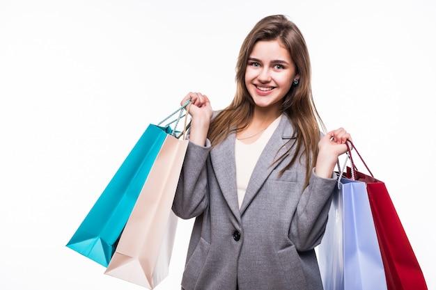 Portret van jonge gelukkig lachende vrouw met boodschappentassen op witte achtergrond