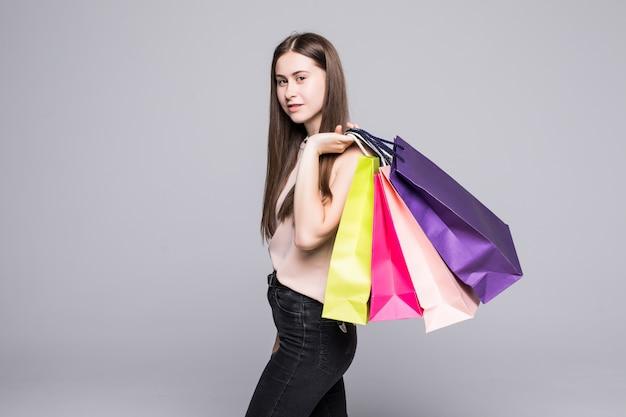 Portret van jonge gelukkig lachende vrouw met boodschappentassen op witte muur