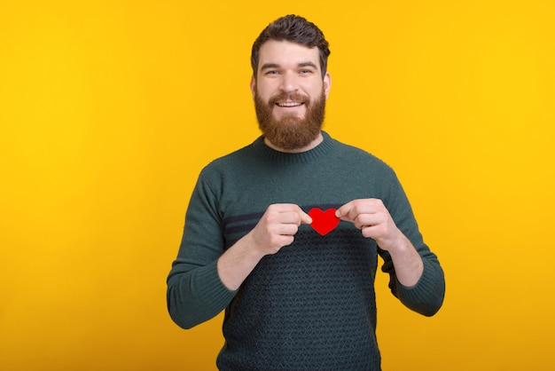 Portret van jonge gelukkig man met rood papier hart over borst