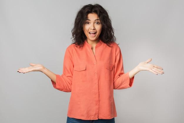 Portret van jonge gelukkig mooie brunette vrouw in oranje shirt, verbaasd gezichtsuitdrukking, geschokt emotie, grappig, hand in hand omhoog, zomerstijl, natuurlijke look`` gemengd ras, geïsoleerd