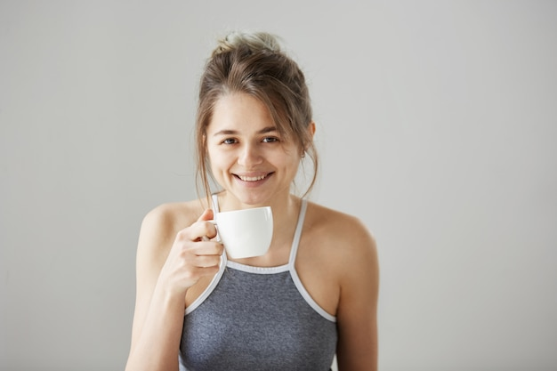 Portret van jonge gelukkig mooie vrouw die lacht bedrijf kopje koffie drinken op ochtend over witte muur.