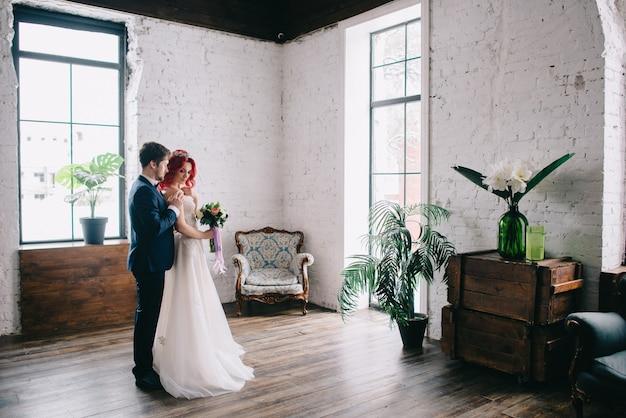 Portret van jonge gelukkig pasgetrouwden in een loft-stijl kamer