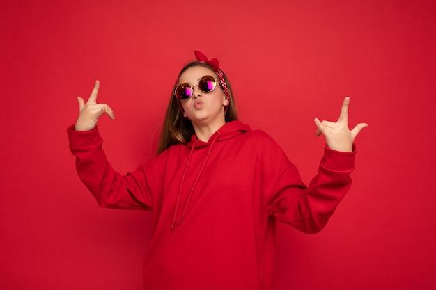 Portret van jonge gelukkig positieve mooie vrouwelijke tiener met oprechte emoties dragen rode hoodie en zonnebril geïsoleerd op rode achtergrond met kopie ruimte en rock-'n-roll gebaar tonen. Premium Foto
