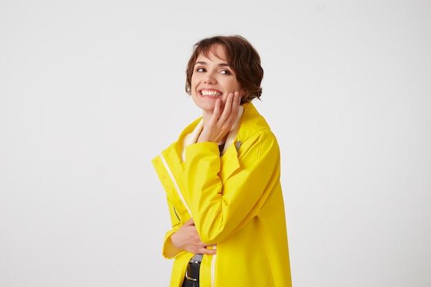 Portret van jonge gelukkig schattig korthaar meisje draagt in gele regenjas, wbroadly glimlacht en kijkt, wang raakt, staat over witte muur.