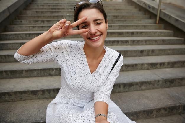 Portret van jonge gelukkige donkerharige vrouw met casual kapsel zittend op betonnen trap buiten, hand opheffen met overwinningsteken en vrolijk glimlachen