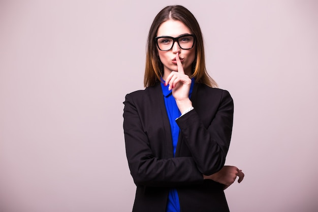 Portret van jonge gelukkige glimlachende bedrijfsvrouw die vinger op haar lippen houdt en vraagt stil te blijven, geïsoleerd over witte muur