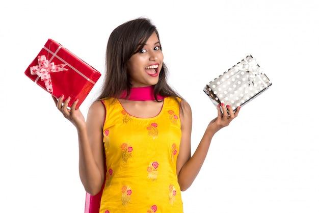Portret van jonge gelukkige het glimlachen indische de giftdozen van de vrouwenholding op wit.