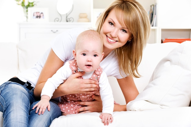 Portret van jonge gelukkige moeder met pasgeboren baby thuis