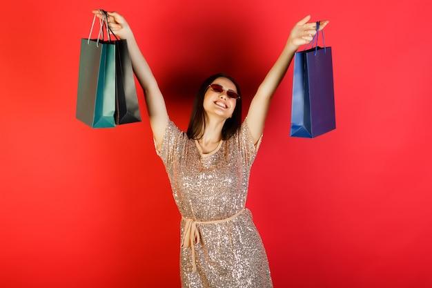 Portret van jonge gelukkige onbezorgde vrouw die kleding draagt die handen omhoog met zakken met winkelen draagt en op rode achtergrond glimlacht.