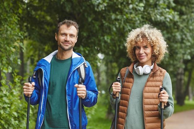 Portret van jonge gelukkige paar glimlachend in de camera tijdens hun wandeling in het bos in zomerdag