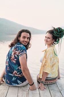 Portret van jonge gelukkige paar zittend op een pier en glimlachend in de camera