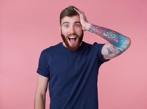 Portret van jonge gelukkige verbaasde aantrekkelijke jonge kerel met rode baard, gekleed in een blauw t-shirt, met wijd open mond van verbazing, hou je hoofd vast, hoorde heel goed nieuws, geïsoleerd op roze achtergrond.