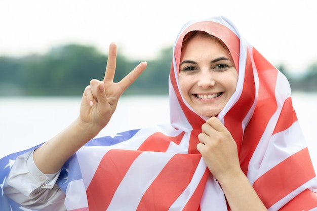 Portret van jonge gelukkige vluchtelingenvrouw met nationale vlag van de vs op haar hoofd en schouders. positief moslimmeisje dat de onafhankelijkheidsdag van de verenigde staten viert. internationale dag van democratie concept.