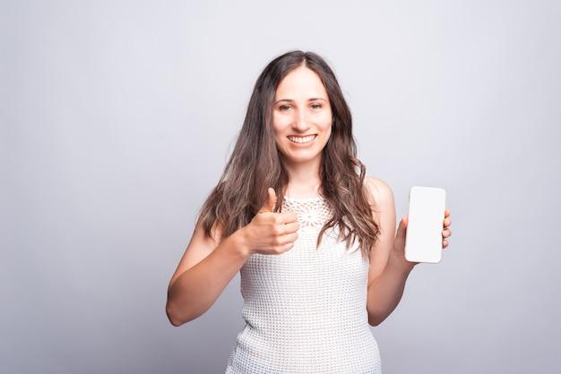 Portret van jonge gelukkige vrouw die duim en het witte lege mobiele scherm toont