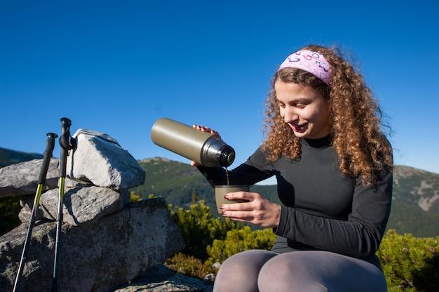 Portret van jonge gelukkige vrouw gieten thee uit thermos
