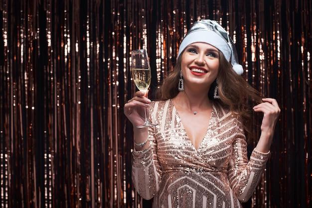Portret van jonge gelukkige vrouw in zilveren kerstmanhoed met champagneglas in handen.