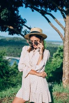 Portret van jonge gelukkige vrouw in zomerjurk, zonnebril en strooien hoed