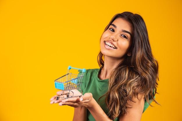 Portret van jonge gelukkige vrouw met winkelmandje op gele achtergrond