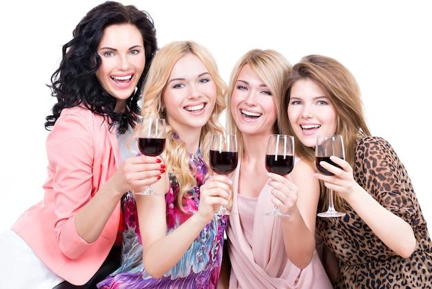 Portret van jonge gelukkige vrouwen die pret hebben en rode die wijn drinken - op wit wordt geïsoleerd