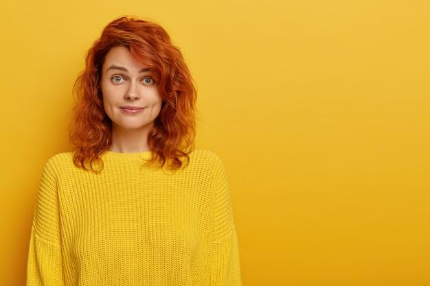 Portret van jonge gember vrouw heeft natuurlijke schoonheid, gekleed in gele gebreide trui, kuiltjes in de wangen kijkt naar de camera met opgetrokken wenkbrauwen, houdt van lichte kleding. warme tinten. kopieer ruimte voor tekst