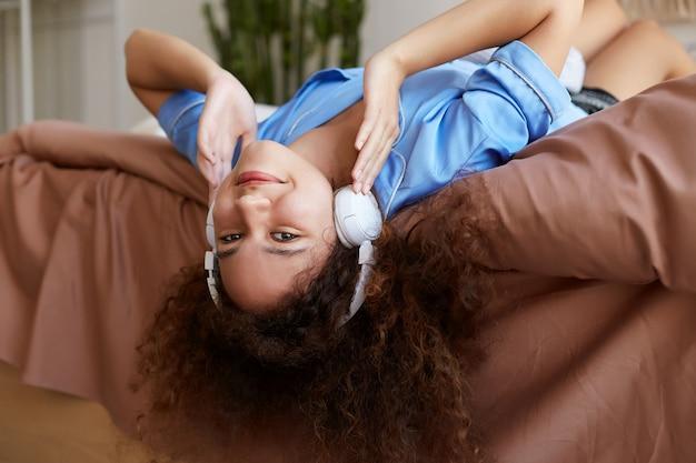 Portret van jonge genieten van krullend mulat meisje liggend op het bed met haar hoofd naar beneden, favoriete muziek in koptelefoon luisteren, glimlachen en ziet er gelukkig uit.