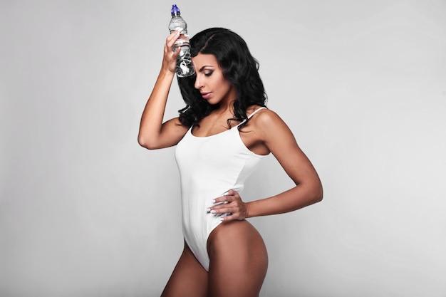 Portret van jonge geschiktheidsvrouw in lichaam met fles
