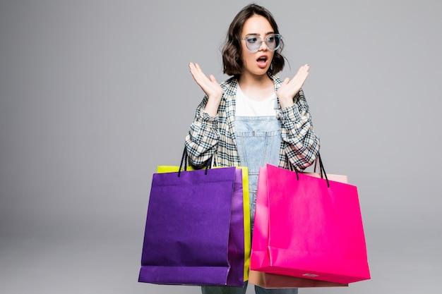 Portret van jonge geschokt shopaholic vrouw met veel boodschappentassen, geïsoleerd