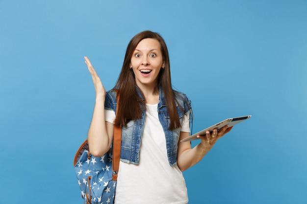 Portret van jonge geschokte verbaasde studente met geopende mond met rugzak gespreide handen houden tablet pc-computer geïsoleerd op blauwe achtergrond. onderwijs op de middelbare school. kopieer ruimte voor advertentie.