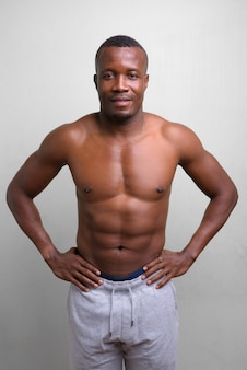 Portret van jonge gespierde afrikaanse man shirtless op wit
