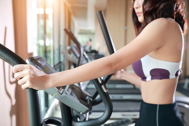 Portret van jonge gezonde en sportieve vrouw die oefeningsmachine in gymnastiek met behulp van