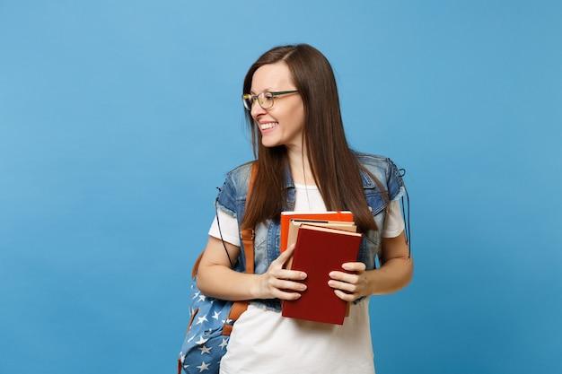 Portret van jonge glimlachende aantrekkelijke gelukkige vrouw student in glazen met rugzak opzij kijken, schoolboeken geïsoleerd op blauwe achtergrond houden. onderwijs in het concept van de middelbare schooluniversiteit.
