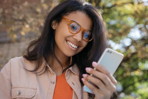 Portret van jonge glimlachende african american vrouw met behulp van mobiele telefoon, communicatie, chatten