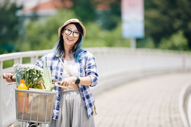 Portret van jonge glimlachende aziatische vrouw die langs de weg met fiets loopt. de mand staat vol met boodschappen en bloemen